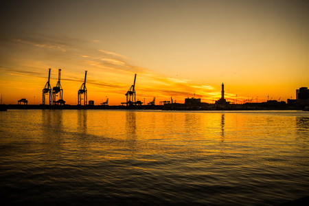 Big cranes silhouette in the port at sunset, Genoa, Italy 스톡 콘텐츠