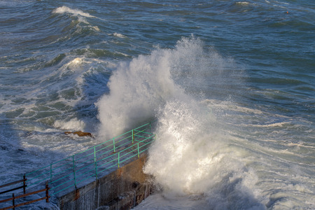 Rough Sea Waves Crashing Over a Pier, mediterranean sea, ligurian coast, Italy.