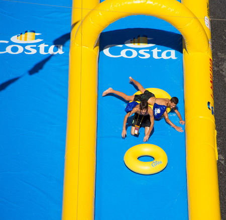 GENOA (GENOVA), ITALY, JULY, 7, 2018 - Two young boys playing in the longest water slide entered in the Guinness Book of Records showed for the Costa Cruises Festival in Genoa (Genoa) city center, Italy.