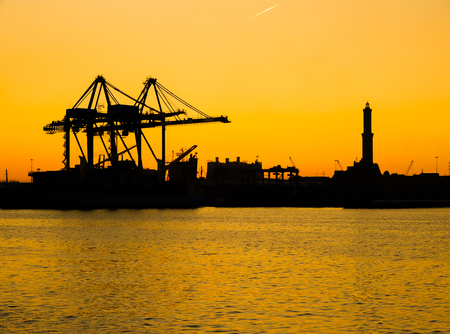 Silhouette of Lanterna (lighhouse) of city of Genoa (Genova), the symbol of the city, in the port at sunset. Italy