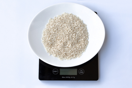 Raw italian rice in a white plate on a black weight scale on a white background.