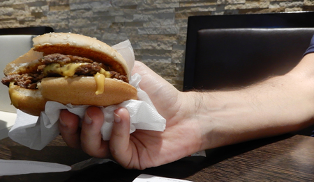 Cooked cheeseburgher showed in a hand