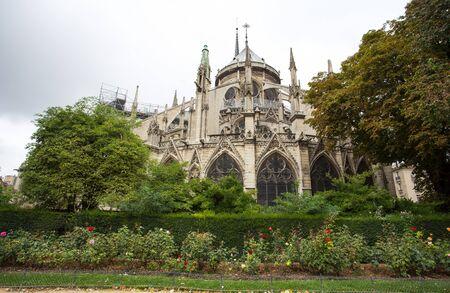 PARIS, FRANCE, SEPTEMBER 6, 2018 - Apse of Notre-Dame de Paris and La fontaine de la Vierge from Square Jean-XXIII. Paris, France