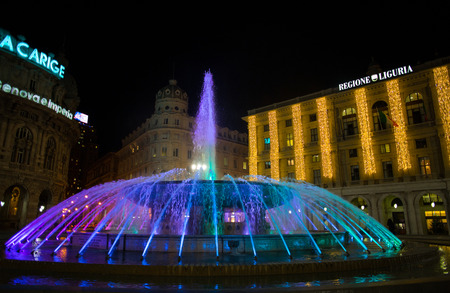 GENOA, ITALY, DECEMBER 11, 2018 - View of the colorful fountain and Palace of the Liguria region of De Ferrari Square by night in Genoa, the heart of the city, Italy. Editorial