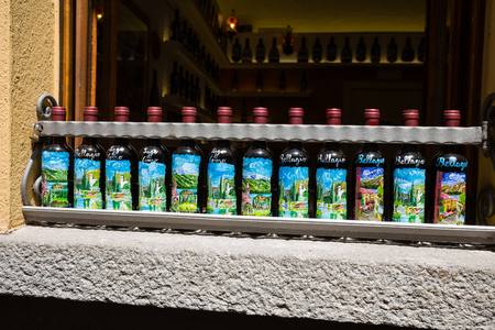 BELLAGIO, ITALY, JUNE 19, 2019 -  Hand painted wine bottles showed outside a restaurant in Bellagio, Italy Editorial