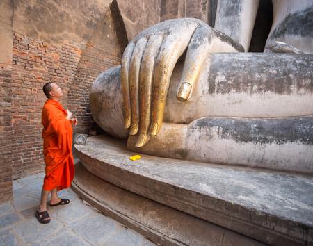 SUKHOTHAI, THAILAND, FEBRUARY, 23, 2017 - Monk praying in front of Big Buddha Statue in Wat Si Chum, Sukhothai Historical Park, Thailand