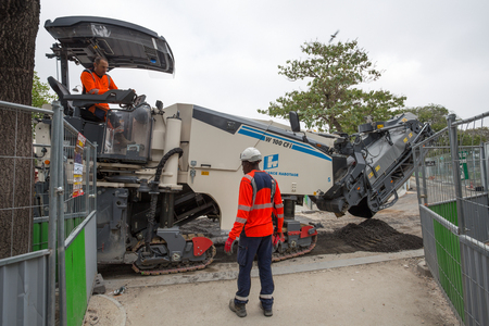 PARIS, FRANCE, SEPTEMBER 5, 2018 - Road workers with a modern machine in Paris, France