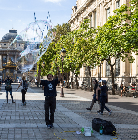 PARIS, FRANCE, SEPTEMBER 9 ,2018 - Unidentified street artist blows huge colorful soap bubbles in Paris on September 9, 2018 Editorial