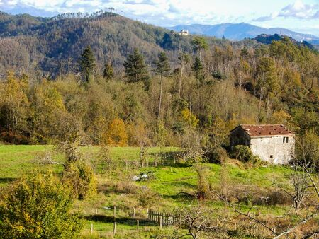 Isolated country house in the meadow with mountains on the background. Standard-Bild - 134071054
