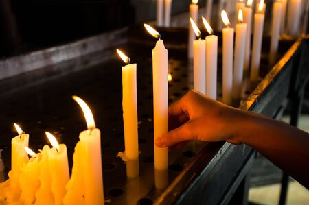 Hand lighting a candle in the church Standard-Bild