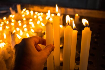 Hand lighting a candle in the church Standard-Bild - 134071575