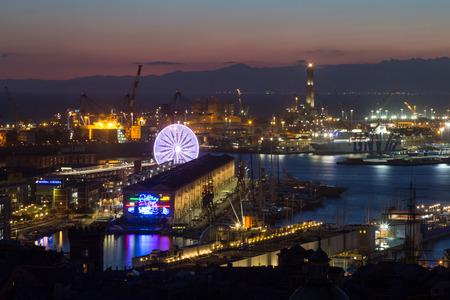 GENOA, ITALY, NOVEMBER  5, 2019 - Aerial view of Genoa, Italy at night, the harbor with the Lanterna, the lighthouse,  symbol of the city, and the ferris wheel, Italy.