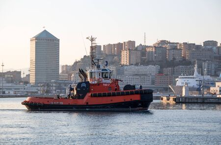 GENOA, ITALY, JANUARY 23, 2020 - A tugboat in the port of Genoa, Italy,  with modern buildings on the background. Editorial