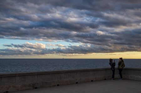 GENOA, ITALY, FEBRUARY 7, 2020 - Two young girls photograph themselves near the sea under a cloudy sky Standard-Bild - 141962103