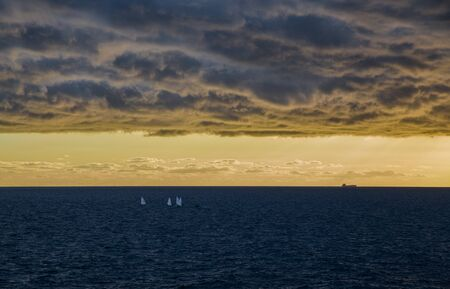 Small sailboats with rough sea under a cloudy sky at sunset