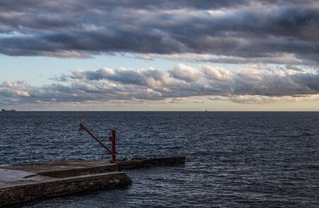 The red crane on the pier under a cloudy sky Standard-Bild