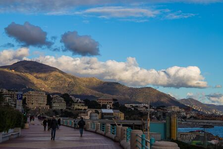 GENOA, ITALY, FEBRUARY 7, 2020 - People walking on the Genoa promenade in a sunny day with a sky with clouds.