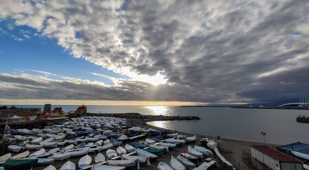 Cloudy sky with sun on Genoa beach with boats in winter time, Italy. Standard-Bild - 141962398