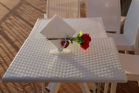 A red rose with an heart on a table with white chairs. Standard-Bild - 141962392
