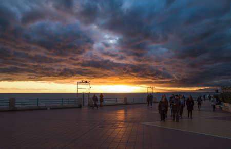 GENOA, ITALY, FEBRUARY 7, 2020 - People walking on the Genoa promenade under a cloudy sky at sunset,  Italy