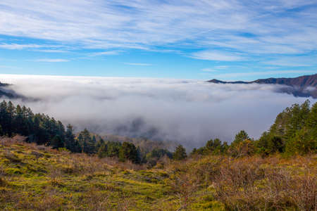 Autumn mountain landscape with low clouds, province of Genoa, Ligurian Alps, Italy.