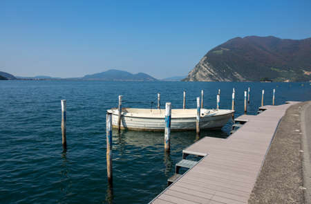 Isolated white boat moored at Monte Isola, Iseo Lake, Brescia province, Lombardy, Italy.