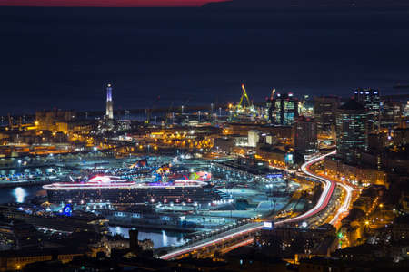GENOA, ITALY, NOVEMBER 18,2020 - Aerial view of Genoa by night, modern buildings, the harbor with the lighthouse and the causeway, Italy