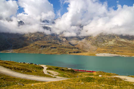 Landscape at Bernina Pass with the White Lake and the red Bernina Express train between Italy and Switzerland in summertime. Фото со стока