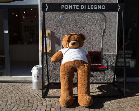 PONTE DI LEGNO, ITALY, SEPTEMBER 9, 2020 - A teddy bear on a rocking chair outside a shop in the village of Ponte di Legno, Brescia province, Italy. Editorial