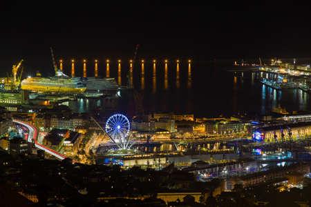 GENOA, ITALY, NOVEMBER 18,2020 - Aerial view of Genoa by night, the ancient harbor with the ferris wheel, Italy
