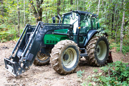 Green tractor in the woods Editorial