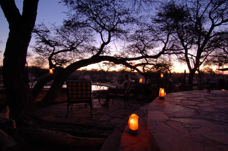 Beautiful african sunset, with swimming pool and acacia tree silhouette. photo