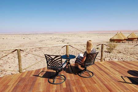 Woman look at the desert - Desert  background. Namibia, Deadvlei, Sossuvlei. photo