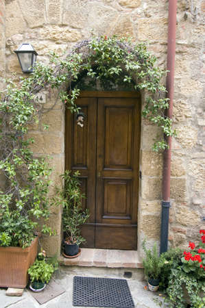 Old wooden door with potted flowers. Italian style. Tuscany Stock Photo