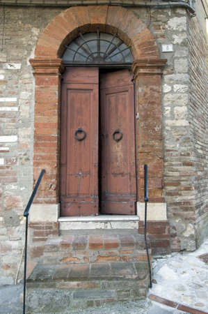 Wooden door with a stone door frame - Open - Tuscany - Italy photo