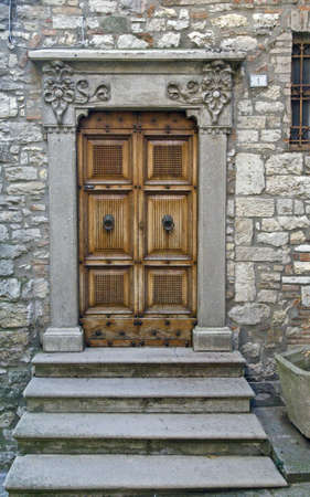 Wooden door with a stone door frame - Tuscany - Italy photo