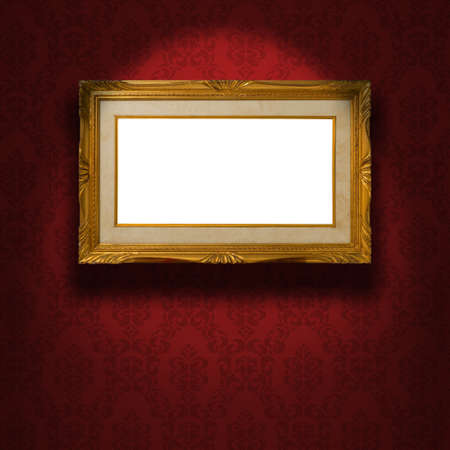 Empty golden frame illuminated from a spotlight. The frame is on the red damask wallpaper photo