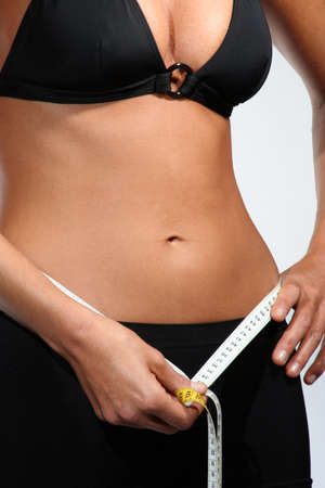 Torso of a woman with measure tape to show weight loss Stock Photo - 11603068