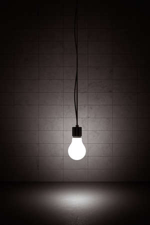 glowing light bulb: Light bulb hanging on a wire with concrete background