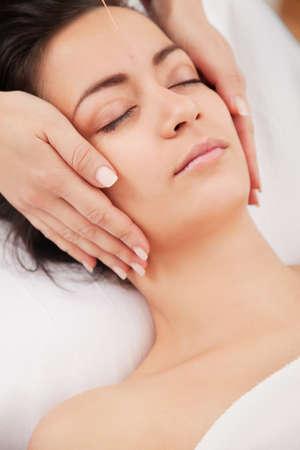 acupuntura china: Las agujas de acupuntura en la cabeza de una mujer joven en el spa