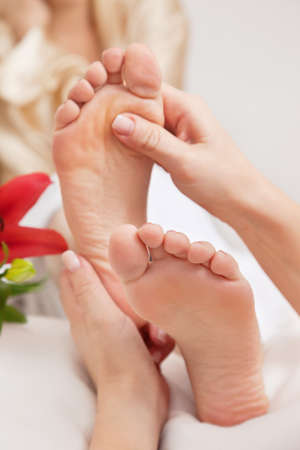 Hands of a reflexologist doing reflexology treatment on the soles of a womans feet
