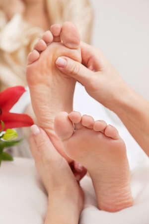 reflexologie: Mains d'un réflexologue faire un traitement de réflexologie sur les semelles de quelques pieds de womans Banque d'images