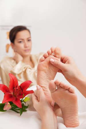 reflexologie plantaire: Mains d'un réflexologue faire un traitement de réflexologie sur les semelles de quelques pieds de womans Banque d'images