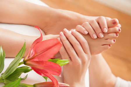 stimulate: Hands of a reflexologist doing reflexology treatment on the soles of a womans feet
