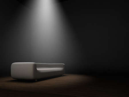Couch in dark room with spotlight from top photo