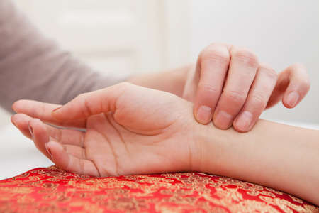 Pulse diagnostica con la mano su un cuscino Archivio Fotografico