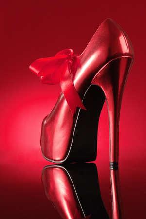 tacones: Zapato rojo sobre fondo rojo con reflejos