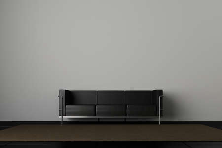 Leather couch in front of a grey wall photo