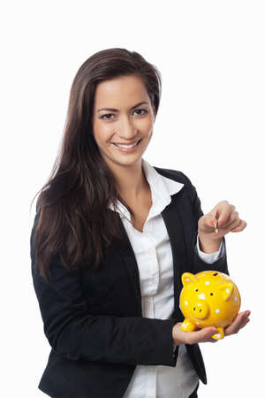 Asian Businesswoman putting money into piggy bank isolated on white photo