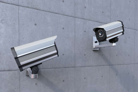 two security camera watching each other on concrete wall photo